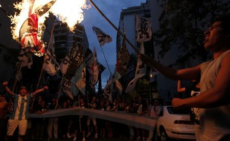 Demonstrators burn a British flag outside the British embassy in Buenos Aires February 2, 2012. Activists protested against the arrival of Britain's Prince William to the Falkland Islands. REUTERS/Marcos Brindicci