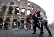 Tourists protect themselves with umbrellas from the falling snow in front of Rome's ancient Colosseum February 3, 2012.    REUTERS/Alessandro Bianchi
