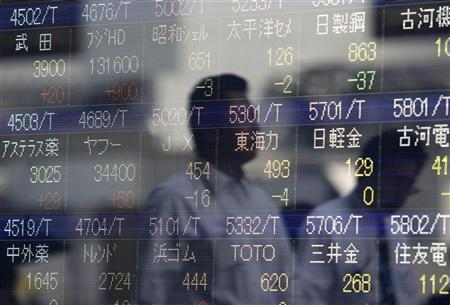 Passers-by are reflected in a stock index board outside a brokerage in Tokyo June 17, 2010. Japan's Nikkei average fell 0.7 per cent after five days of gains, coming off one-month highs, though support was expected to hold at the level of the benchmark's 25-day moving average. REUTERS/Issei Kato
