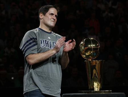 Dallas Mavericks owner Mark Cuban applauds next to the Larry O'Brien Championship trophy during a ceremony before their NBA basketball game with the Miami Heat in Dallas, Texas December 25, 2011.  REUTERS/Mike Stone