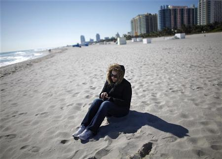 A tourist wearing a jacket sit at the beach in South Beach Miami, Florida January 11, 2010. REUTERS/Carlos Barria