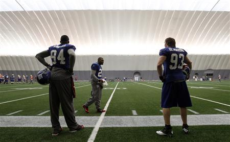 New York Giants players Mathias Kiwanuka (94), Derrick Martin (C), and Chase Blackburn (93) wait on the sidelines during practice for the Super Bowl XLVI in Indianapolis, February 2, 2012. The New York Giants will play the New England Patriots on February 5.  REUTERS/Jeff Haynes