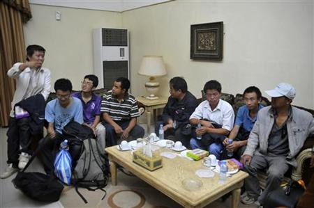 Chinese workers who escaped after being abducted sit after arriving at Khartoum Airport January 30, 2012. REUTERS/Stringer