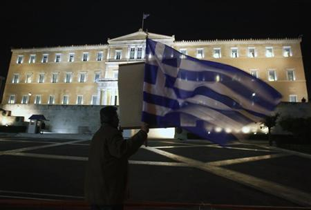 An anti-government protester holds a Greek flag as he shouts slogans against Greek Premier George Papandreou and his lawmakers in front of the parliament during a debate prior to a vote of confidence in Athens November 3, 2011.    REUTERS/Yannis Behrakis