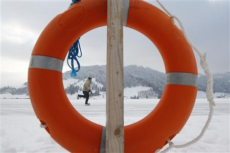 A man skates on the frozen lake Sihl (Sihlsee) past a life buoy on a freezing cold afternoon, outside Euthal, near Einsiedeln, February 4, 2012. Temperatures dropped to as low as minus 11 degrees Celsius (12.2 degrees Fahrenheit) in Switzerland and other parts of Europe.  REUTERS/Christian Hartmann