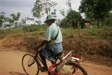 A man rides his bicycle past a sign indicating the economic zone near Dawei in southern Myanmar, near the site of a planned special economic zone and deep sea port, November 19, 2011. REUTERS/Staff
