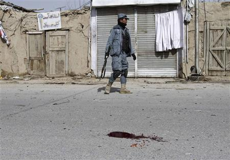 An Afghan policeman keeps watch next to a blood stain after a car bomb blast in the city of Kandahar February 5, 2012. The car bomb in the south Afghan city of Kandahar killed at least seven people and wounded 19 on Sunday, the province's media office said. REUTERS/Ahmad Nadeem