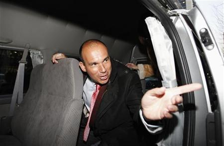 Former Olympus CEO Michael Woodford speaks to a reporter from inside a van as he leaves a news conference at the Japan National Press Club in Tokyo January 6, 2012.  REUTERS/Issei Kato