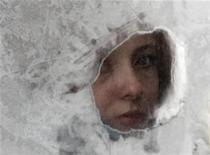 Женщина выглядывает из заледеневшего в мороз окна маршрутки в Киеве 6 февраля 2012. Украину, пережившую неделю рекордных за последние шесть лет морозов, ждет новая волна холода с температурами до минус 30 градусов, прогнозирует украинский Гидрометеоцентр. REUTERS/GLEB GARANICH