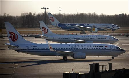 Air China planes pass each other on the tarmac and runway at Beijing International Airport February 6, 2012.     REUTERS/David Gray
