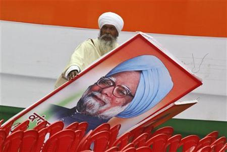 A supporter of India's ruling Congress party hold a billboard of India's Prime Minister Manmohan Singh after an election campaign rally ahead of state assembly elections at Moga, Punjab January 19, 2012. REUTERS/Ajay Verma