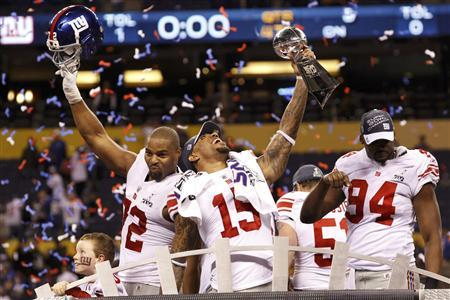 New York Giants wide receiver Devin Thomas (C) holds the Vince Lombardi Trophy and celebrates with teammates Osi Umenyiora (L) and Mathias Kiwanuka after the Giants defeated the New England Patriots in the NFL Super Bowl XLVI football game in Indianapolis, Indiana, February 5, 2012. REUTERS-Mike Segar