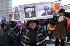 Мужчина держит плакат на акции протеста в Бухаресте 2 февраля 2012. Премьер-министр Румынии Эмиль Бок в понедельник ушел в отставку после нескольких недель широких протестов по всей стране, вызванных жестким экономическим курсом его правительства. REUTERS/Radu Sigheti