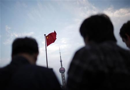 People stand near a Chinese flag as the Oriental Pearl TV tower is seen in the financial area of Pudong in Shanghai, November 1, 2011.  REUTERS/Carlos Barria