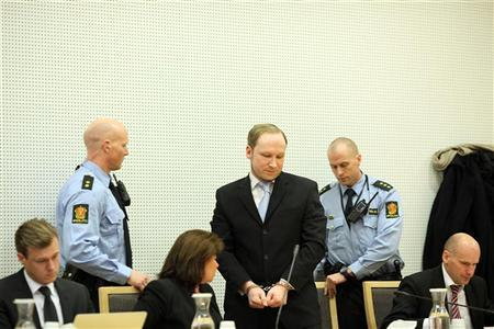 Norwegian confessed killer Anders Behring Breivik (C) is seated next to his defence lawyers Geir Lippestad (R) and Vibeke Hein Baera (3rd L) at a hearing at a courthouse Oslo February 6, 2012.  REUTERS/Christopher Olssan