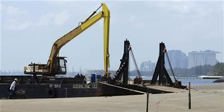 A man works at the site of a breakwaters upgrade along East Coast Park in Singapore January 4, 2012.  REUTERS/Tim Chong