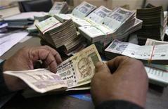 """Работник банка в индийском городе Агартала пересчитывает купюры 31 декабря 2010 года. Государственный банк Индии, крупнейший кредитор в стране, будет публиковать в газетах имена и фотографии """"злостных"""" неплательщиков, чтобы заставить их вернуть одолженные средства, написала столичная газета Economic Times. REUTERS/Jayanta Dey"""