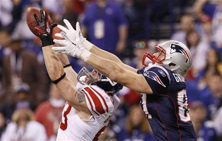 New York Giants middle linebacker Chase Blackburn (L) intercepts a pass intended for New England Patriots tight end Rob Gronkowski during the third quarter  in the NFL Super Bowl XLVI football game in Indianapolis in the NFL Super Bowl XLVI football game in Indianapolis, Indiana, February 5, 2012.  REUTERS/Mike Segar