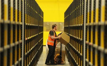 A worker lifts a box at Amazon's new fulfilment centre after it was opened by Scotland's First Minister Alex Salmond in Dunfermline, Scotland, November 15, 2011.The warehouse covers more than one million square feet (93,000 square metres), about the size of 14 soccer pitches, and is Amazon?s biggest in the United Kingdom. It will create 750 permanent jobs, along with a further 1,500 temporary jobs during peak periods.  REUTERS/Russell Cheyne (BRITAIN - Tags: POLITICS BUSINESS)