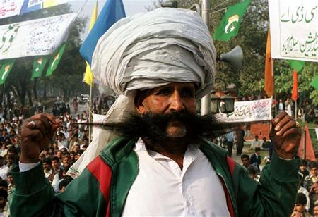 Ellahi Bakhsh Baluch, a Pakistani renowned for his thick mustache, poses on a stage during a nationl flag rally in Islamabad November 30 1998.  REUTERS/Stringer .