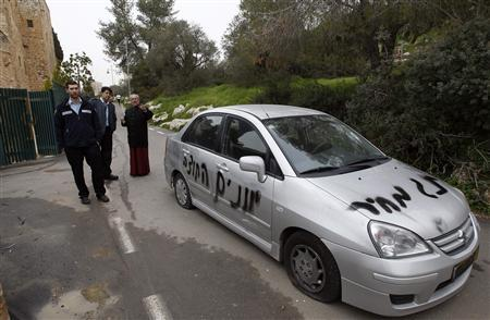 Israeli police officers stand with a priest beside a car that was sprayed with graffiti outside the Monastery of the Cross, which was also defaced with graffiti, in Jerusalem February 7, 2012