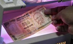 Сотрудник банка проверяет подлинность купюры в Аллахабаде, 16 декабря 2011 г. Рост индийской экономики может замедлиться до уровня ниже 7 процентов в текущем финансовом году и стать минимальным с кризисного 2008 года из-за действий центробанка, направленных на борьбу с инфляцией, и политического кризиса. REUTERS/Jitendra Prakash