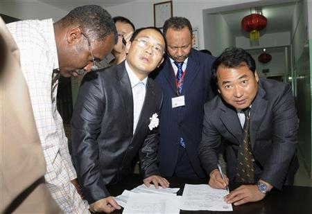 Chinese Embassy representatives sign handover papers to receive the body of a Chinese worker killed during a kidnapping, from a Sudanese Red Crescent representative (L) and a Sudanese Foreign Ministry official at the Chinese-run Hawasha hospital in Khartoum February 7, 2012. REUTERS/Mohamed Nureldin Abdallah
