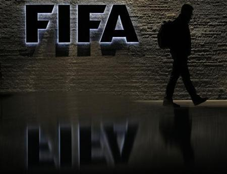 A man is silhouetted as he makes his way past the main entrance of FIFA headquarters, the Home of FIFA, in Zurich October 20, 2010. REUTERS/Christian Hartmann