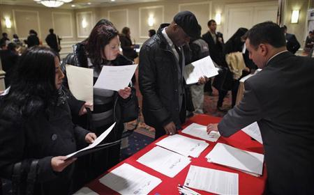 People talk with a job recruiter (R) while they attend the ''JobEXPO'' job fair in New York, January 25, 2012.  REUTERS/Eduardo Munoz