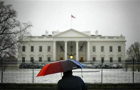 A man uses an umbrella as shelter from the snow in front of the White House in Washington, December 5, 2007.  REUTERS/Jim Young