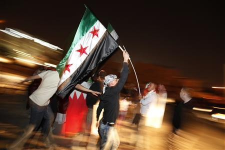 An anti Assad regime protester waves Syrian revolution flag as he participates in a protest outside the Syrian Embassy in Manama February 7, 2012. REUTERS/Hamad I Mohammed