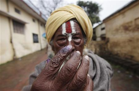 A Hindu holy man shows his ink-marked finger after casting his vote at a polling station in Ayodhya during the state assembly election, in the northern Indian state of Uttar Pradesh February 8, 2012. REUTERS/Adnan Abidi