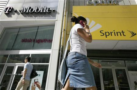 A woman talks on her phone as she walks past T-mobile and Sprint wireless stores in New York in this July 30, 2009 file photo. REUTERS/Brendan McDermid