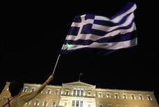 Участник акции протеста размахивает греческим флагом у здания парламента страны в Афинах 21 июня 2011 года. Греческие партии в среду снова попытаются согласовать программу реформ в обмен на новую финансовую помощь, чтобы не допустить неконтролируемого дефолта, но постоянный срыв дедлайнов заставляет лидеров еврозоны рассуждать о выходе Афин из валютного клуба. REUTERS/Yiorgos Karahalis