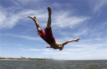 A boy dives into the Rio de la Plata (River Plate) to cool off in Montevideo November 23, 2011. REUTERS/Andres Stapff