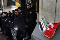 Турецкие полицейские стоят рядом с миниатюрными флагами Турции и сирийской оппозиции, установленными у входа в консульство Сирии в Стамбуле во время акции протеста 5 февраля 2012 года. Сирийские войска продвинулись глубже в мятежный город Хомс в среду, уничтожив, по подсчетам активистов оппозиции, десятки мирных жителей. ООН призвала к экстренным мерам для их защиты, а Турция, по-видимому, готова усилить давление на президента Башара Асада. REUTERS/Murad Sezer