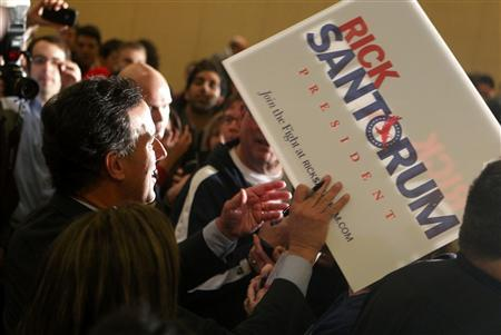 Rick Santorum prepares to autograph a campaign sign for a supporter at his primary night rally at the St. Charles Convention Center in St. Charles, Missouri, February 7, 2012.  REUTERS/Sarah Conard