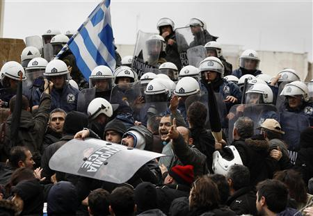 Anti-austerity protesters carry a police shield during scuffles in front of the parliament in Athens February 7, 2012.  REUTERS/Yannis Behrakis