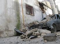 <p>The remains of a wrecked vehicle are seen next to a damaged house in the Sunni Muslim district of Bab Amro in Homs in this picture received February 8, 2012. REUTERS/Mulham Alnader/Handout</p>