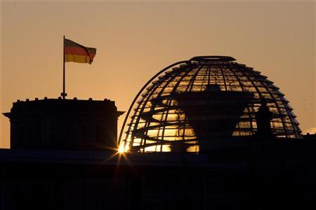 The sun rises behind the cupola of the Reichstag building, the seat of the German lower house of parliament, on a sunny cold day  in Berlin, February 1, 2012.  REUTERS/Thomas Peter