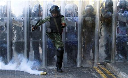 An army officer kicks a tear gas cannister during a clash with the supporters of ousted Maldivian president Mohamed Nasheed in Male February 8, 2012. REUTERS/Dinuka Liyanawatte