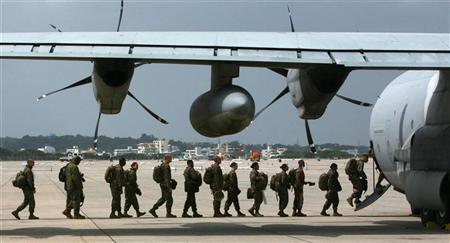 Marines assigned to Marine Aircraft Group 36, 1st Marine Aircraft Wing, III Marine Expeditionary Force, board a KC-130J Super Hercules aircraft to provide assistance to areas in Japan affected by last week's massive earthquake and tsunami, Marine Corps Air Station Futenma, Okinawa March 16, 2011. REUTERS/U.S. Marine Corps/Cpl. Justin Wheeler/Handout