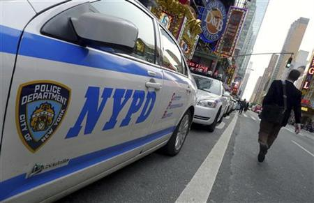 A pedestrian walks past a line of New York Police Department (NYPD) cars parked at Times Square in New York, October 18, 2011.   REUTERS/Gary Hershorn