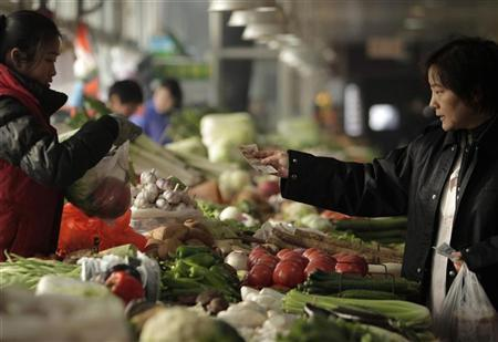 A customer pays for her vegetables at a market in Beijing January 12, 2012. REUTERS/Soo Hoo Zheyang