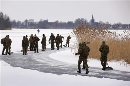 A regiment of 50 soldiers sweep the ice on the lake near Woudsend, south of Leeuwarden February 8, 2012. REUTERS/Michael Kooren