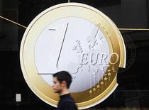 Человек проходит мимо изображенной на витрине пиццерии монеты евро в Мадриде 9 декабря 2011 года. Евро достиг нового двухмесячного максимума в четверг на ожиданиях, что Греция наконец-то договорится о новой программе помощи, несмотря на то, что греческие партии не смогли утвердить необходимые меры экономии к утру четверга. REUTERS/Susana Vera