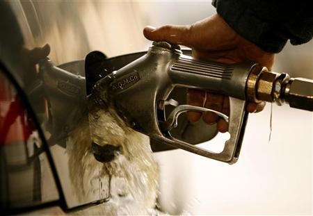 Fuel overflows as an Iranian man pumps gasoline into his car at a gas station in Tehran January 21, 2007. REUTERS/Caren Firouz/Files