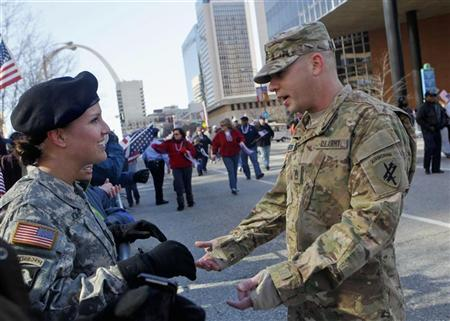 Sgt. Audrey Johnsey (L) greets Sfc. Joshua Herbig (R) who she served with in Afghanistan, during the Welcome Home Heroes Parade in downtown St. Louis, Missouri January 28, 2012. REUTERS/Sarah Conard