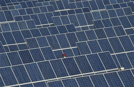 An employee walks between rows of solar panels at a solar power plant on the outskirts of Dunhuang, China, June 10, 2011. REUTERS/Stringer
