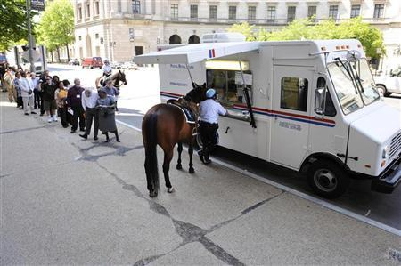U.S. Park Police Officer Calvin Covington stands at the front of the line with his horse Harper to mail his family's income tax returns at a mobile post office near the Internal Revenue Service building in downtown Washington, April 15, 2010.    REUTERS/Jonathan Ernst